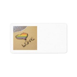 Corazón gay del amor del arco iris en la arena etiqueta de dirección