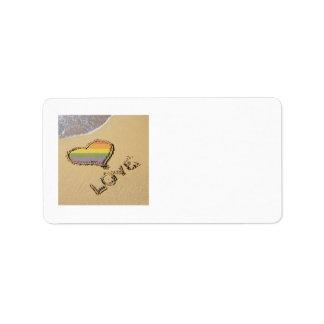 Corazón gay del amor del arco iris en la arena etiquetas de dirección