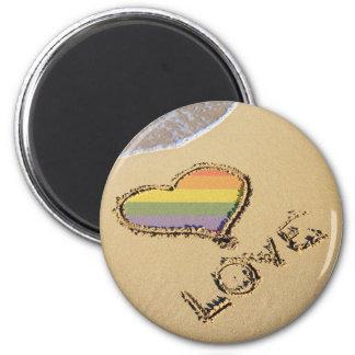 Corazón gay del amor del arco iris en la arena iman para frigorífico