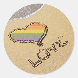 Corazón gay del amor del arco iris en la arena pegatina redonda