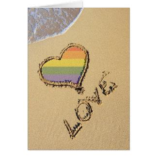 Corazón gay del amor del arco iris en la arena tarjeta de felicitación