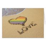 Corazón gay del amor del arco iris en la arena tarjetón