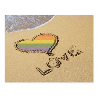 Corazón gay del amor del arco iris en la arena tarjetas postales