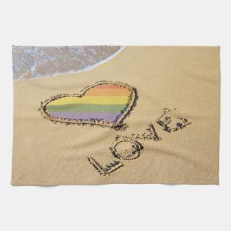 Corazón gay del amor del arco iris en la arena toallas de cocina