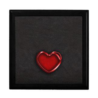 Corazón metálico rojo en el cuero negro caja de recuerdo