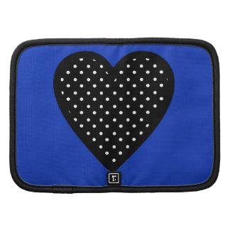 Corazón negro con los lunares en fondo azul planificador