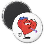 Corazón rojo enfermo con un termómetro en su boca iman