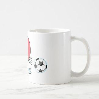 Corazón rojo sano que juega con el balón de fútbol tazas de café