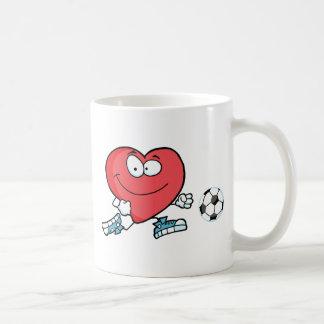 Corazón rojo sano que juega con el balón de fútbol tazas