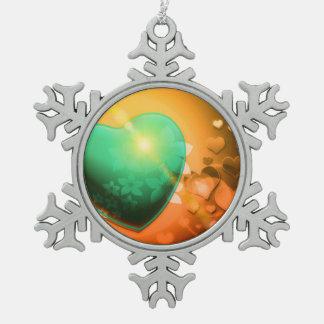 Corazón y trébol verdes anaranjados del fondo w de adorno de peltre en forma de copo de nieve