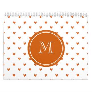 Corazones anaranjados quemados del brillo con el calendarios de pared