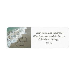 Corazones de la arena que entrelazan en la playa etiqueta de remite