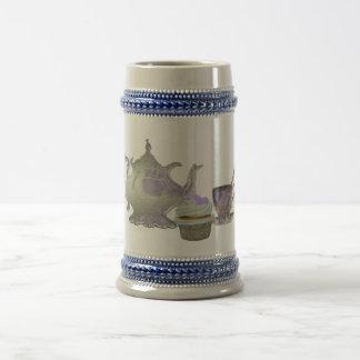 Corazones de la magdalena de la lila, tetera y jarra de cerveza