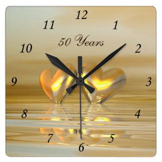 Corazones de oro del aniversario reloj cuadrado