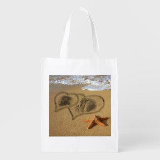 Corazones del perrito en la arena bolsas para la compra