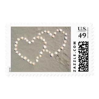 Corazones del Seashell en los sellos de la arena