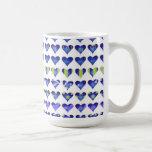 Corazones púrpuras, azules y verdes frescos en bla tazas de café