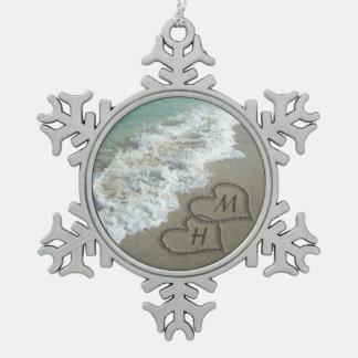 Corazones que entrelazan en la arena de la playa adorno de peltre en forma de copo de nieve