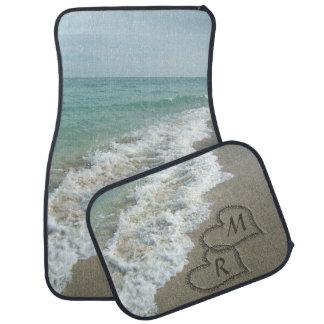 Corazones que entrelazan en la arena de la playa alfombrilla de auto
