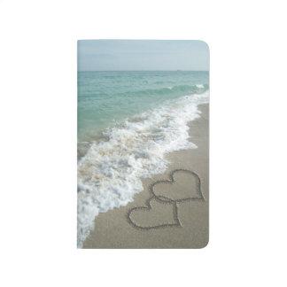 Corazones que entrelazan en la arena de la playa cuadernos