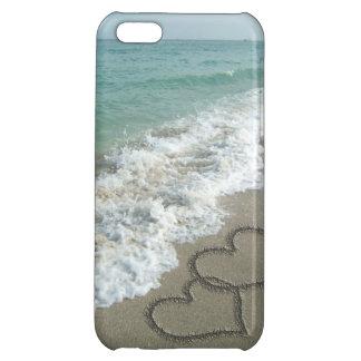 Corazones que entrelazan en la arena de la playa