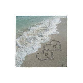 Corazones que entrelazan en la arena de la playa imán de piedra