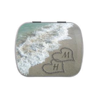 Corazones que entrelazan en la arena de la playa latas de dulces