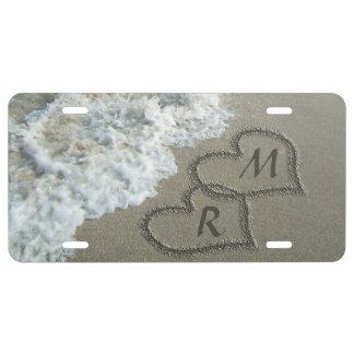 Corazones que entrelazan en la arena de la playa placa de matrícula