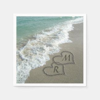 Corazones que entrelazan en la arena de la playa servilleta de papel