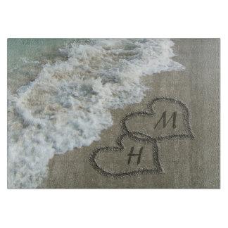Corazones que entrelazan en la arena de la playa tablas de cortar