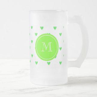 Corazones verdes claros del brillo con el taza de cristal