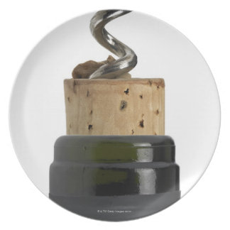 Corkscrew and cork, photographed on white plates