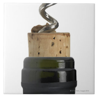 Corkscrew and cork, photographed on white large square tile