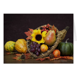 Cornucopia del otoño con las uvas, la pera y las tarjeta de felicitación