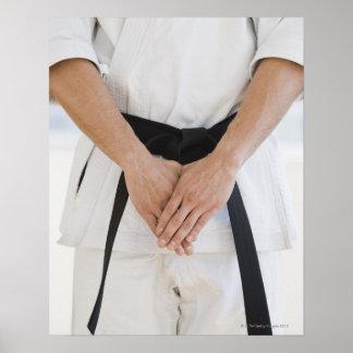 Correa negra del karate del hombre que lleva póster