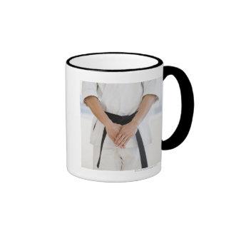 Correa negra del karate del hombre que lleva taza