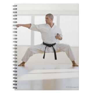 Correa negra del karate masculino hispánico en libretas espirales