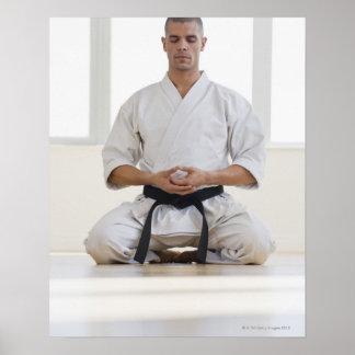 Correa negra del karate masculino hispánico medita posters
