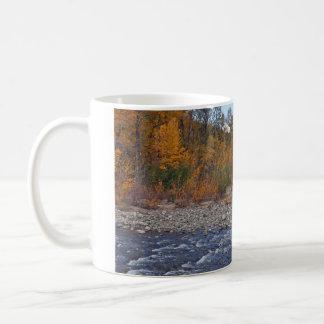 Corriente de la montaña en taza de café de la