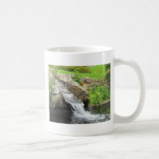 Corriente del agua que corre sobre rocas taza de café
