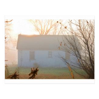 Cortijo viejo en niebla en la salida del sol postal