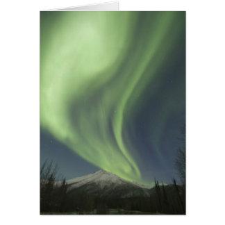 Cortinas de los borealis verdes de la aurora en el tarjeta de felicitación