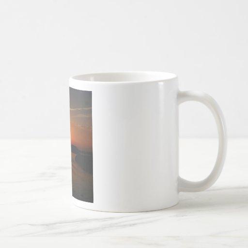 Costa rocosa oscura de la puesta del sol de la nat tazas