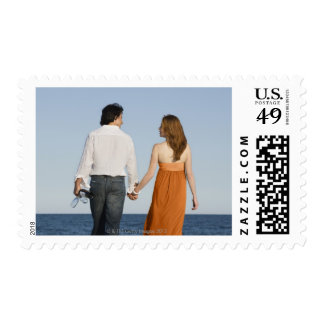 Couple holding hands and walking on beach postage