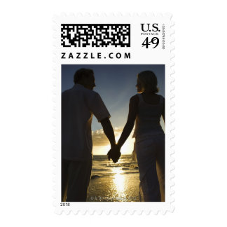 Couple holding hands on beach at sunset stamps
