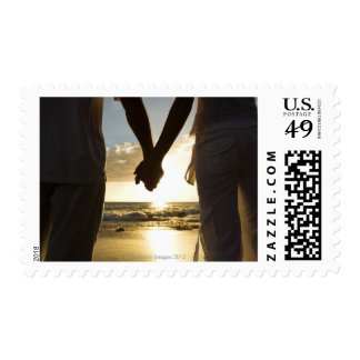 Couple holding hands on beach stamps