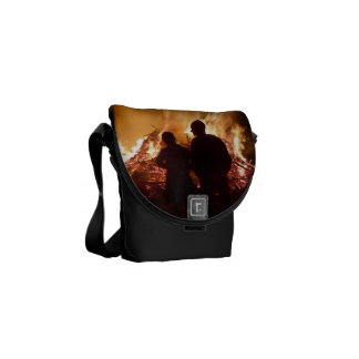 Couple in front of campfire courier bags