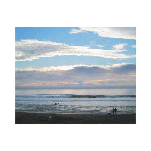 Couple on Beach Gazing into Sunset and Ocean Canvas Print