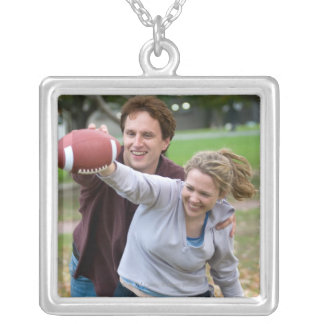 Couple playing football in park square pendant necklace