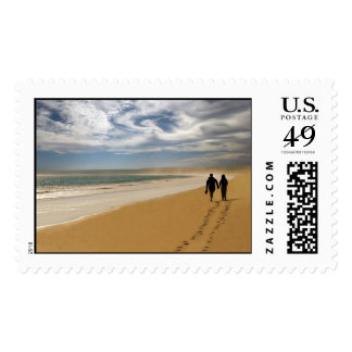 Couple walking on the beach postage stamp